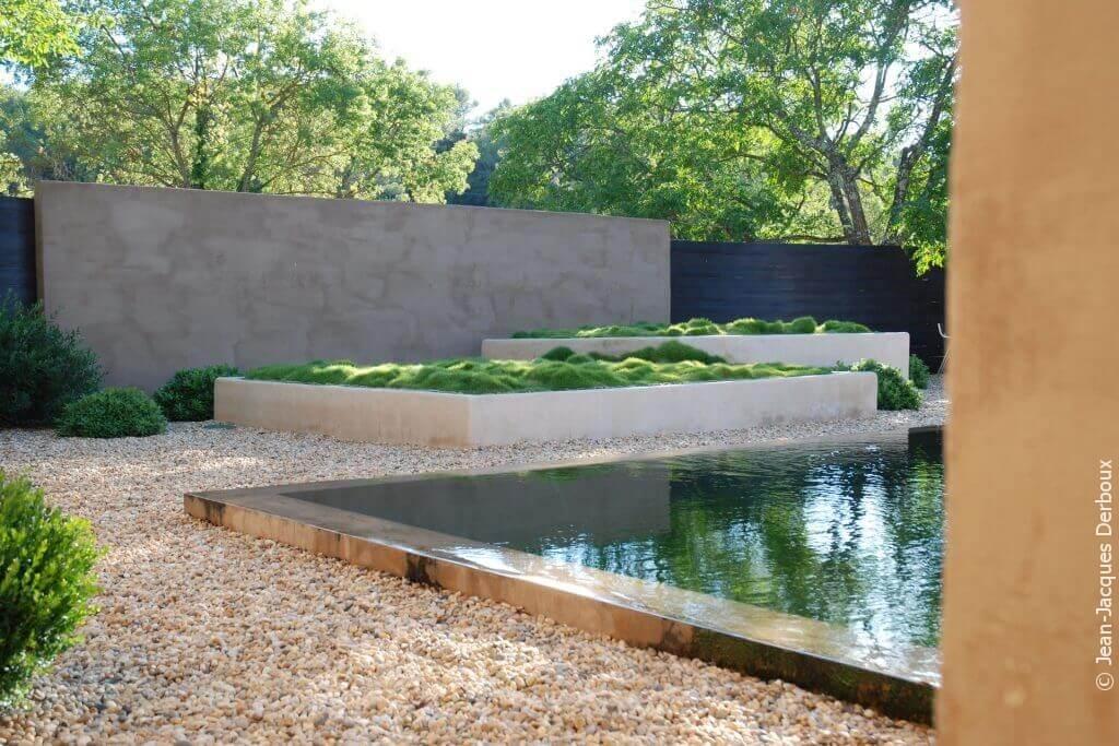 Piscine biologique à débordement, eau effet miroir, grande jardinière maçonnée plantée de zoysia, gravier.