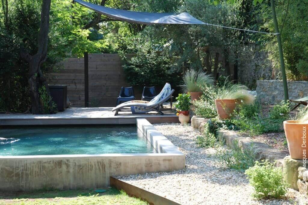 Piscine maçonnée, enduit ciment, terrasse bois, mobilier, bain de soleil, ombrage toile, pots décoratifs.