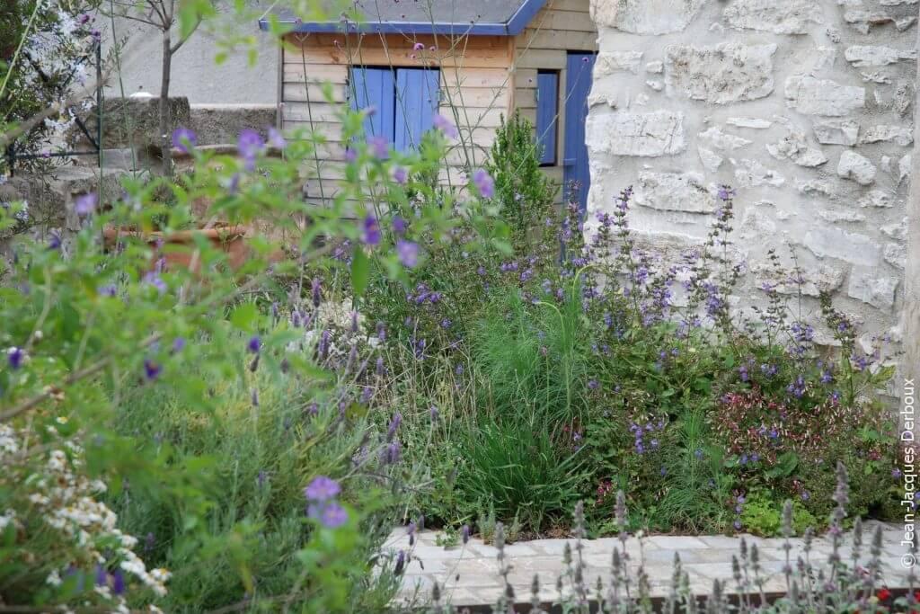 Cabane au jardin, volets bleus, fleurs mauve, esprit champêtre.
