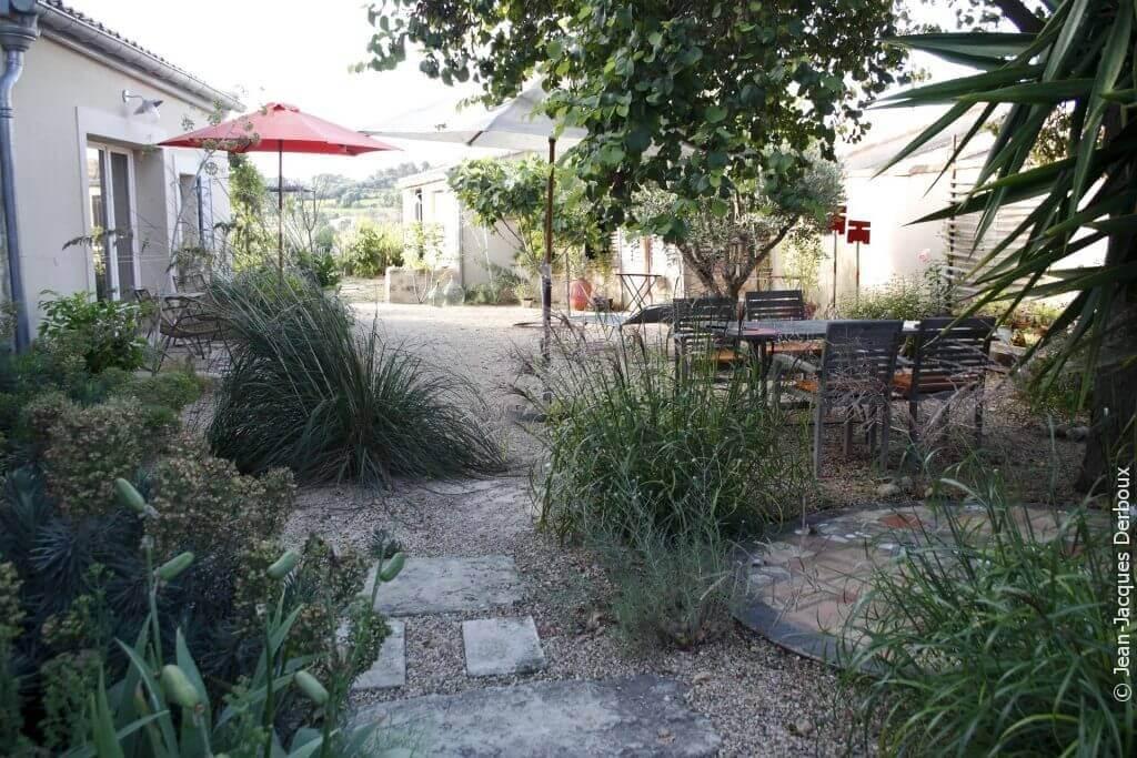 Jardin du sud, courette du Languedoc, à l'ombre des parasols et des arbres, mobilier de jardin, gravier, jardin écologique, dalle en pierre dans gravier, figuier.